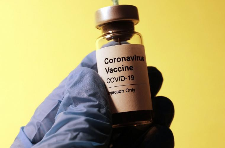 A close up of a gloved hand holding a corona vaccine vial against a yellow background