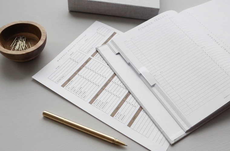 A finance tracker notebook with pen